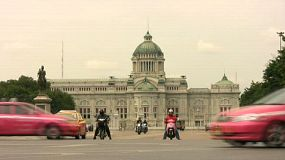 A shot of traffic in front of the Ananta Samakhorn Throne Hall, the famous palace of King Rama V in Bangkok, Thailand.