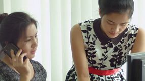 Two young Asian female coworkers working together at a computer in the office.
