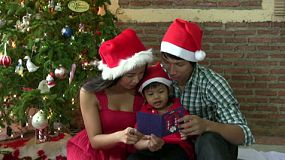 A lovely Asian family take a moment to read a Christmas card with their beautiful Thai son.