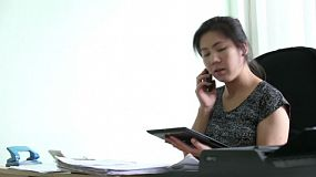 An attractive Asian female young adult office manager efficiently runs her office in Bangkok, Thailand.