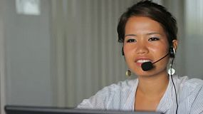 An attractive Asian girl works at a busy call center in Bangkok, Thailand.
