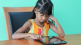 A cute little seven year old Asian girl has fun playing games on her new digital tablet.