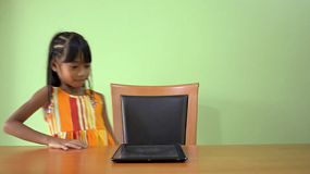 A cute young Asian girl, walks in and sits down at the table, then starts using a tablet pc.