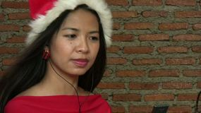 A close up shot of a beautiful Asian girl wearing a cute Santa Hat listening to Christmas music.