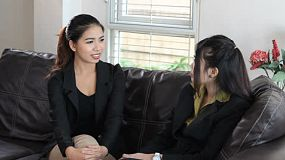 An attractive Asian woman talks to her friend and co-worker on a break at the office in Bangkok, Thailand.
