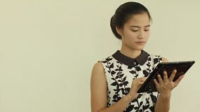 A beautiful young Asian woman in a dress playing on a tablet computer.