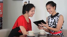 Two attractive Asian young adult women enjoy spending time together and chatting over coffee in a cafe in Bangkok, Thailand.