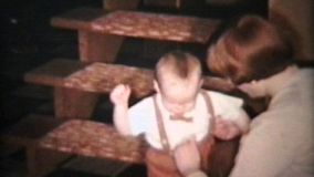 A cute little baby boy wearing suspenders gets ready to eat Christmas dinner with the family.
