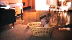 An adorable baby boy plays with his mother's yellow laundry basket.