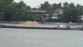 A barge filled with sand floating up a river in Bangkok, Thailand.