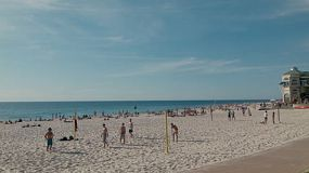 A group of friends playing beach volleyball at Cottesloe Beach in Western Australia.