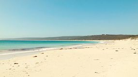 Looking along the sandy beach at Hamelin Bay in Australia's South West, with some seaweed washed ashore.