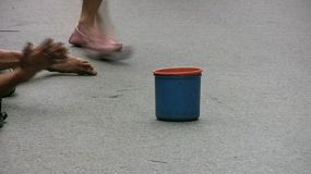 A little boy begging with a blue cup on the streets of Bangkok, Thailand.