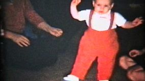 A cute little baby boy wearing red suspenders learns to walk with the help of his mommy and grandmother.
