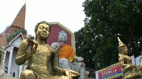 Large Buddha statues with garland in front of the Buddhist temple in Bangkok, Thailand.