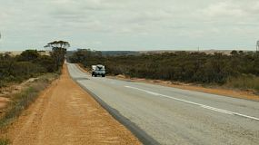 An SUV towing a caravan down an empty and straight highway in country Australia.