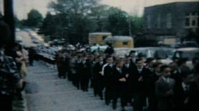 Catholic school grads walk down the street in a processional in Pennsylvania.