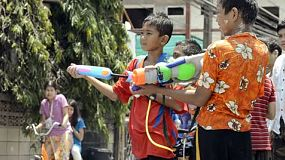 Bangkok, Thailand - April 13, 2012: Children enjoying the annual Songkran festivities with a water fight spraying passing motorbikes.  Songkran is traditionally the Thai New Year, and as part of the celebrations, pouring water over other people is done as a way of blessing them. This has escalated to major water fights on the streets, with people pouring water on, or throwing water over anyone who passes by.  [binicons]293727 h 21 icon[/binicons]