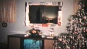 A shot of a living room that has been decorated for Christmas including presents under the tree. (Vintage 8mm film)