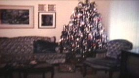 A shot of a living room that has been decorated for Christmas including presents under the tree.