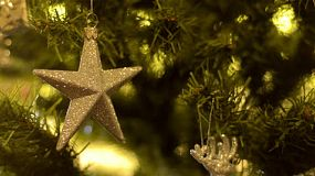 A golden star ornament decoration hanging on a christmas tree.