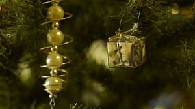 A golden box and other decorations hanging on a christmas tree