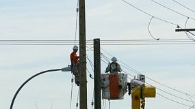 VANCOUVER, BC, OCTOBER 2015: A pair of hydro repair linemen work together to resolve various issues on a telephone pole in suburbia in the city of Vancouver.