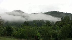 Clouds and mist begin to vanish in the jungle hills of Chantaburi, Thailand.