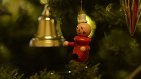 A clown and golden bell hanging on a christmas tree.