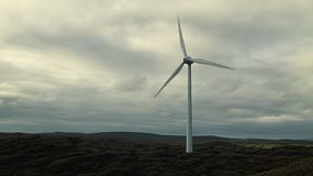 A wind turbine on a coastal wind farm against cloudy skies.