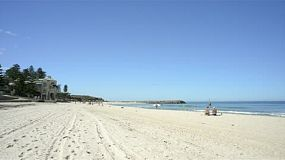Cottesloe beach in Perth, Western Australia, on a quiet summer day, with people enjoying the popular beach to escape the heat.