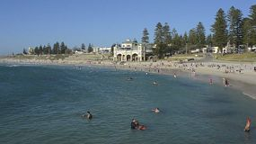 People swimming and enjoying the cool break at Cottesloe Beach in Perth, Western Australia, on a hot summer day.