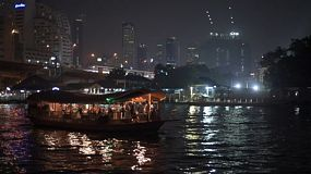 Passing by a boat cruise on the Chao Phraya River in Bangkok at night.