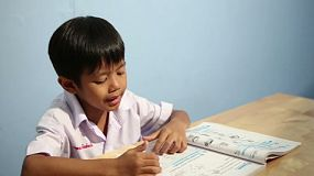 A cute Asian boy spends time reading his school book at home in Bangkok, Thailand.