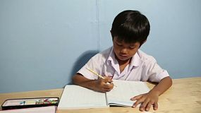 A cute Asian boy spends time finishing his school work at home in Bangkok, Thailand.