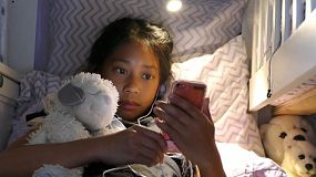 A cute little Asian girl enjoys spending time in her home made fort in her bedroom reading and using her device and hanging out with her puppy.