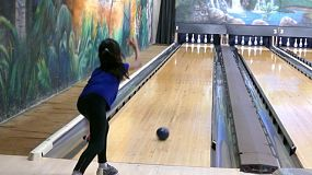 A shot of a young Asian girl throwing a bowling ball and hitting the pins down in a bowling alley.