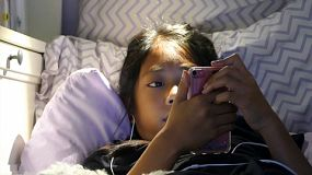 A very sleepy little Asian girl enjoys spending time in her home made fort in her bedroom listening to music and watching videos on her device while trying hard to not fall asleep.