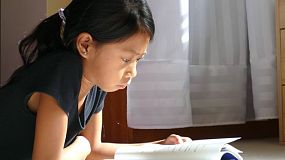A cute little Asian girl enjoys reading her book and doing homework in her sunbeam in the afternoon.