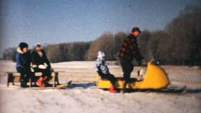 A family enjoys a beautiful winter's day snowmobiling at the family farm in 1964.