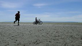 "A father and daughter stop and pose for a ""selfie"" while cycling together on a sand bar at the beach on a gorgeous sunny summer day."