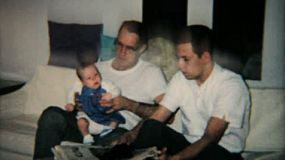 A father and son spend some quality time with their new little baby girl in 1965.