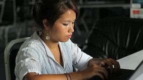 A pretty Asian girl does her office work on the company lap top.