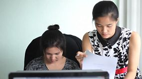 Two attractive Asian female young adult office workers collaborate together as they work in the office in Bangkok, Thailand.