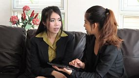 Two attractive female Asian office workers using a tablet to discuss a work project in Bangkok, Thailand