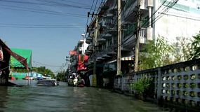 A boat navigates past submerged cars down a flooded street of Bangkok, Thailand during the floods of 2011.