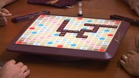 Several friends playing a fun game of Scrabble on a revolving table top.