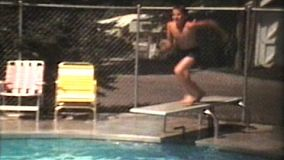 Three siblings have fun swimming in the pool and jumping off the diving board in the middle of a hot summer.