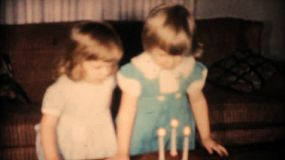A cute little three year old girl blows out the candles on her birthday cake with the help of her sister in 1961.