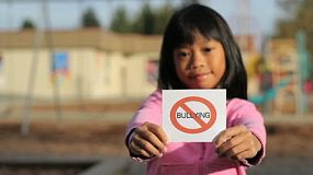 A cute Asian girl holds up a NO BULLYING sign in front of a school.